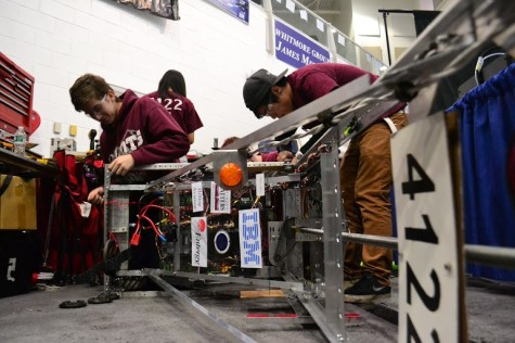 Team members making last minute adjustments to the robot before competition.