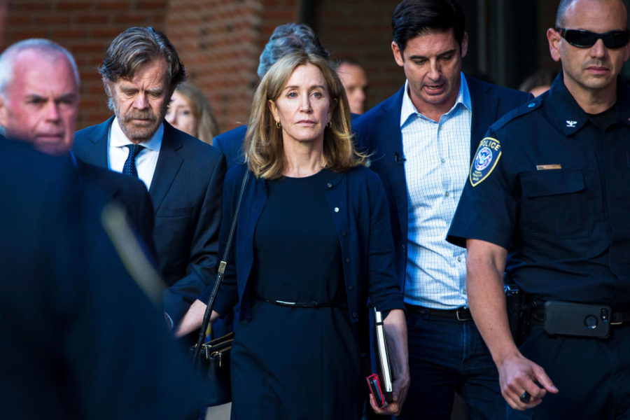 BOSTON, MA - SEPTEMBER 13: Felicity Huffman, right, and her husband, William H. Macy, walk out of John Joseph Moakley United States Courthouse in Boston, MA on Sept. 13, 2019. Huffman was sentenced to 14 days in prison and community service for her role in the college admissions scandal. (Photo by Nic Antaya for The Boston Globe via Getty Images)